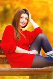 Portrait girl relaxing on bench in autumnal park. Stock Photo