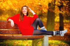 Portrait girl relaxing on bench in autumnal park. Royalty Free Stock Image