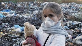 Portrait of a girl in a respirator at the dump