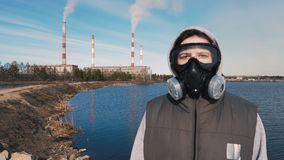 Portrait of a girl in a respirator or gas mask. In the background smoke comes from the pipes of a hydroelectric power stock footage