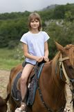 Portrait of a girl riding a brown horse. Walk in nature stock photos