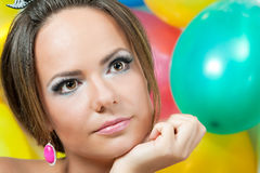 Portrait - a girl's face on a bright background. Close up a portrait, against multi-coloured balloons Royalty Free Stock Images