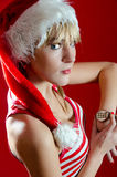 Portrait of Girl in Santa's cap with watch. Portrait of Polish girl wearing Santa Claus Cap - looking on her watch Royalty Free Stock Image