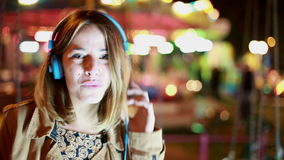Portrait of girl shaking her head to the rhythm of music with headphones stock video footage