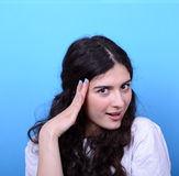 Portrait of girl with shock gesture looking up against blue back Royalty Free Stock Images