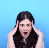 Portrait of girl with shock gesture looking up against blue back Stock Photography