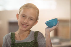 Portrait of girl showing bowl in pottery workshop Royalty Free Stock Photo