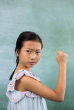 Portrait of girl showing fist in classroom. Portrait of girl showing fist against board in classroom Royalty Free Stock Photos