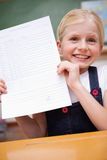 Portrait of a girl showing her school report Stock Images
