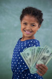 Portrait of girl showing paper currency against wall Stock Photography