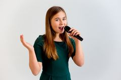 Girl singing with a microphone stock images