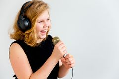 Girl singing with a microphone royalty free stock photos