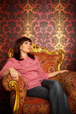 Portrait of girl sitting in armchair. Retro style. Portrait of girl sitting in armchair. Interior in retro style. Looking aside. Vertical format Stock Images
