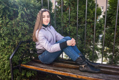 Portrait of a girl sitting on the beanch in the park. Cute young teenage girl resting on a bench in autumn Park Royalty Free Stock Photography