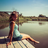 Portrait of a girl sitting on a bridge near the water Royalty Free Stock Photos