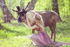 Portrait of a girl sitting in a fabulous dress next to a reindeer Royalty Free Stock Images