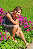 Portrait of the girl sitting  among red flowers Stock Photos