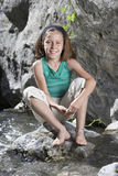 Portrait Of Girl Sitting On Rock By Stream Royalty Free Stock Photography