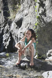Portrait Of Girl Sitting On Rock By Stream Stock Photo