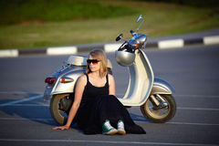Portrait of a girl sitting by scooter Royalty Free Stock Photo