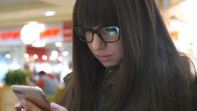 Portrait of girl sitting in the shopping mall and using smartphone. Young woman in glasses looking at the phone and. Surfing the internet. Screen of cellphone stock video footage