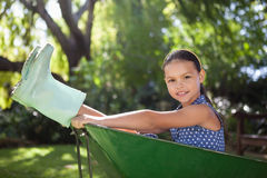 Portrait of girl sitting in wheelbarrow at backyard. Portrait of girl wearing rubber boots sitting in wheelbarrow at backyard Royalty Free Stock Image