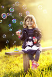 Portrait of a girl sitting on a wooden bench blows bubbles in th Stock Images