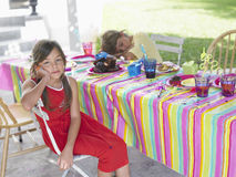 Portrait Of Girl By Sleeping Boy At Birthday Party. Portrait of a girl with boy sleeping at outdoor table after birthday party Stock Image
