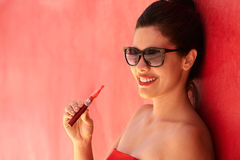 Portrait Girl Smokes Electronic Cigarette E-Cig Against Red Back Royalty Free Stock Images