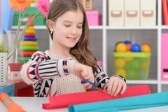 Girl snipping paper. Portrait of girl snipping colorful paper with scissors Stock Photo