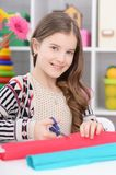 Girl snipping paper. Portrait of a girl snipping colorful paper with scissors Royalty Free Stock Image