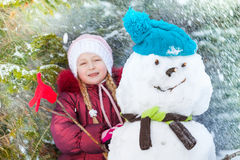 Portrait of a girl with snowman and snow flakes Royalty Free Stock Photos