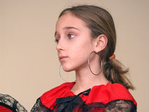 Portrait of a girl with spanish earrings and red dress with black lace.  Royalty Free Stock Photography