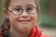 Portrait of a girl with special needs in glasses close-up. In nature stock image