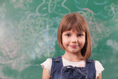 Portrait of girl standing in front off drawn chalkboard in elemen Royalty Free Stock Image