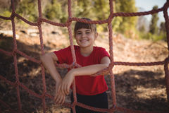 Portrait of girl standing near net during obstacle course. In boot camp stock photos