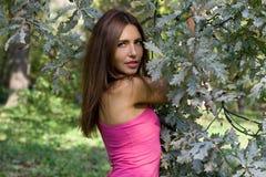 Portrait of a girl standing near oak tree Stock Images