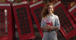 Portrait of girl standing outdoors smiling looking at camera. On the background English red telephone booths. Travelling stock footage