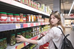 Portrait of a girl standing in a supermarket near a canned vegetable counter and looking into the camera royalty free stock photo