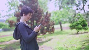 Portrait girl dreams and writes a message on the smartphone. Portrait girl stands in a city park, dreams and writes a message on a smartphone stock video footage