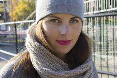 Portrait of a girl on the street in the autumn. The girl dressed in a hat and scarf Stock Photo