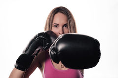 Portrait of a girl striking blow in boxing gloves isolated on white.  Royalty Free Stock Photos