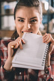 Portrait of girl student biting copybook Royalty Free Stock Images