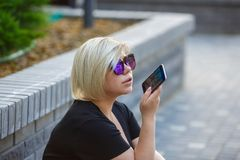 Portrait girl student outdoors talking on phone. Portrait young girl student in sunglasses plus size sits in the yard on campus, talking on the phone with royalty free stock photo