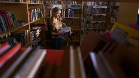 A portrait of girl student reading a book in the. Library. very keen on, leafing through a book. the camera moves left to right, slow motion stock video footage