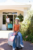 Portrait of girl (6-8) on suitcase in front of house, mother with luggage in background Royalty Free Stock Photo