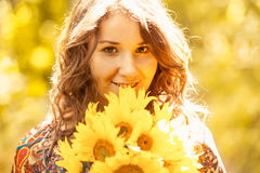 Portrait of girl with sunflowers posing in sun rays Royalty Free Stock Images