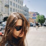 Portrait of a girl with sunglasses against the background of the city with flying hair in the wind