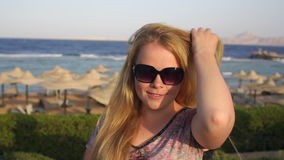 Portrait of a girl in sunglasses on the beach. Young woman in sunglasses with flowing blonde hair stands on the beach against the sea and beach umbrellas stock footage