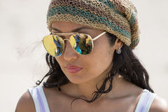 Portrait of a girl in sunglasses. And a knitted cap on the beach Royalty Free Stock Images